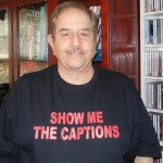black shirt with red lettering saying Show Me the Captions
