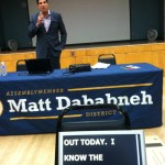 photo of Assemblyman Dababneh, California Town Hall Meeting shows screen at front of stage with Live Captioning in action - speech to text used by audience